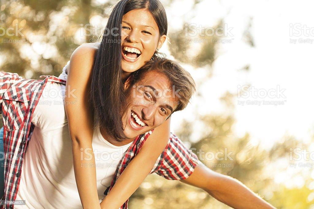 Young man giving woman piggyback ride stock photo