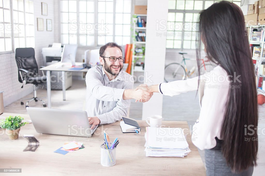 Young man greeting a new female coworker stock photo