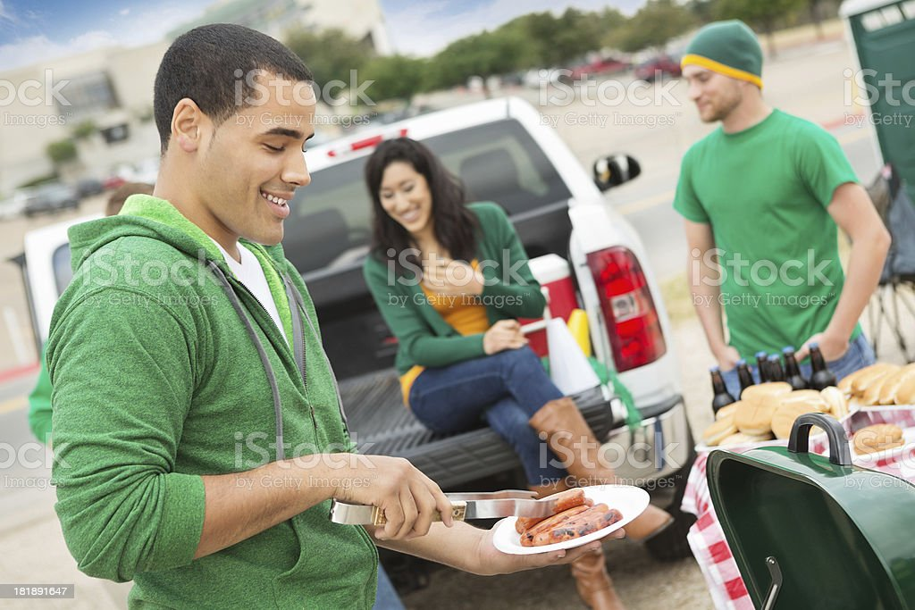 Young man grilling during tailgating party near football stadium stock photo