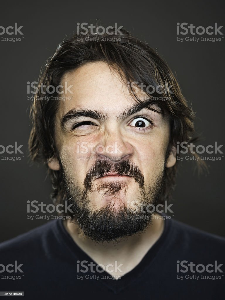 Young man grimacing stock photo