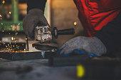 Young man grinding metal close up shot