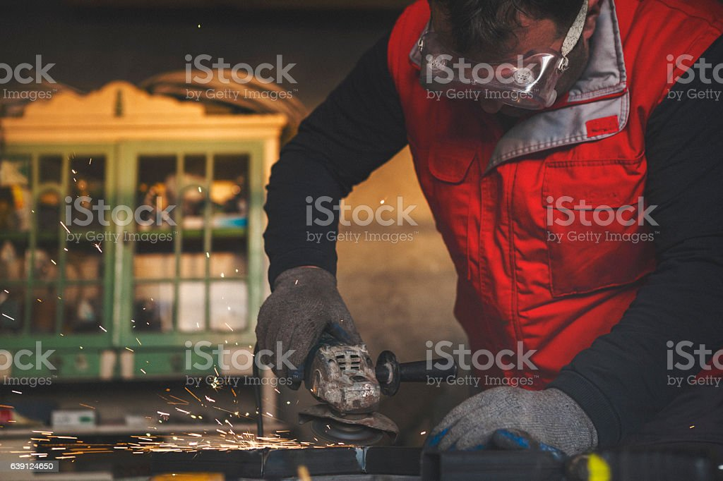 Young man grinding metal stock photo