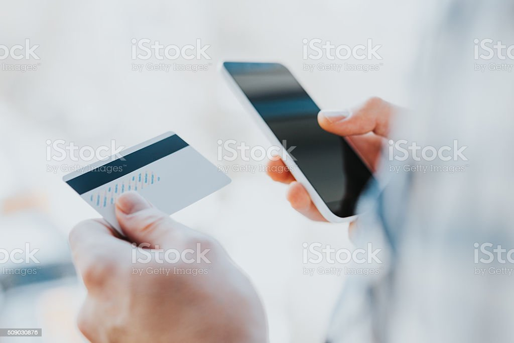 young man hands holding credit card and using phone stock photo