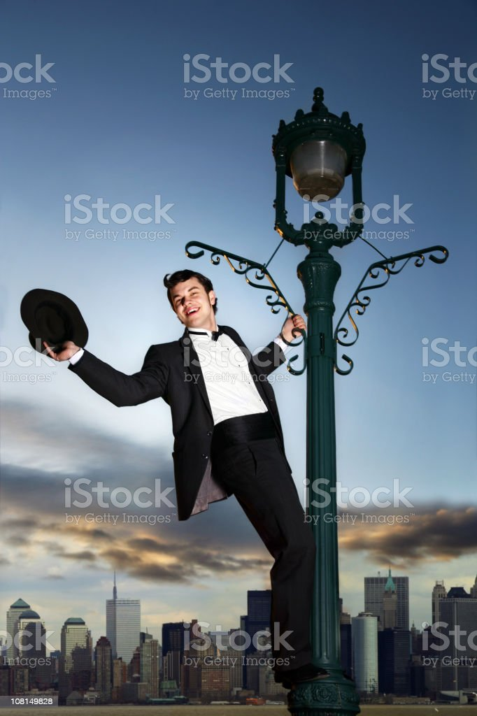Young Man Hanging from Light Post in NYC royalty-free stock photo