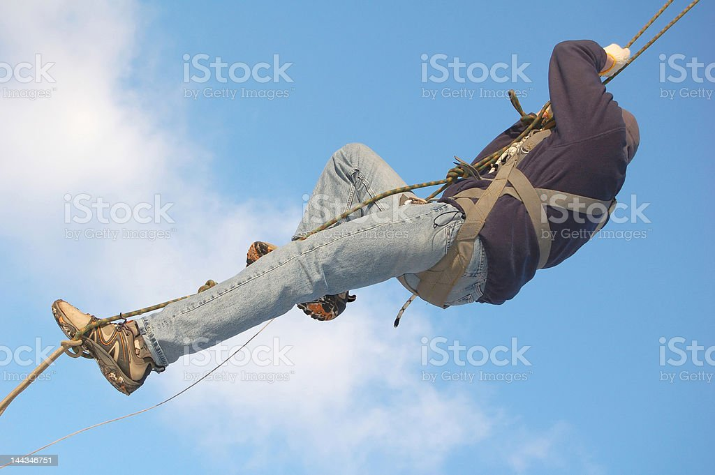 Young man hanging on the rope in blue sky royalty-free stock photo