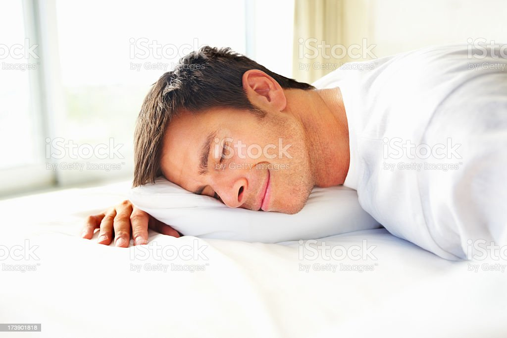 Young man has fallen asleep on a bed royalty-free stock photo