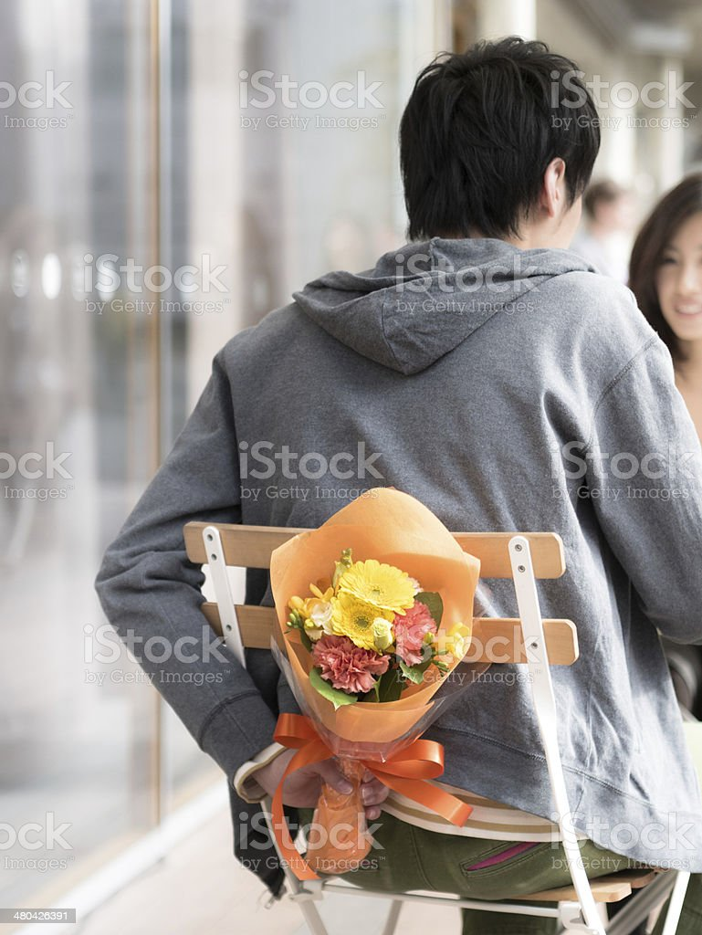 Young man having a bouquet behind his back stock photo