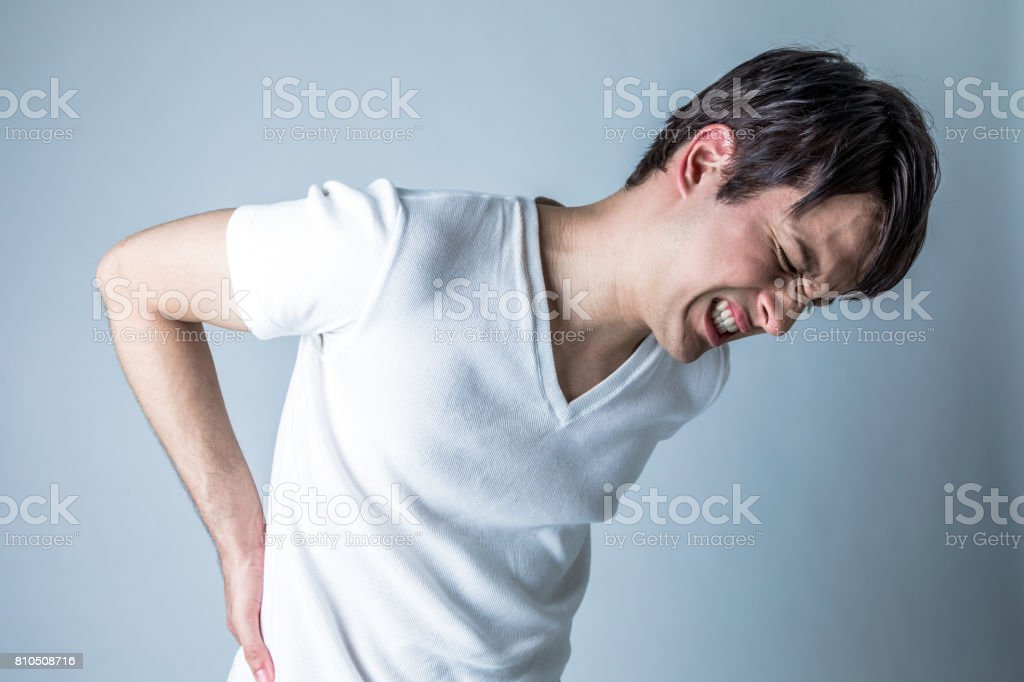 young man having a pain in lower back stock photo
