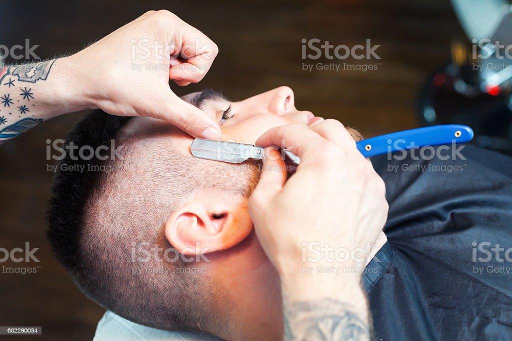 Young man having beard shaven stock photo