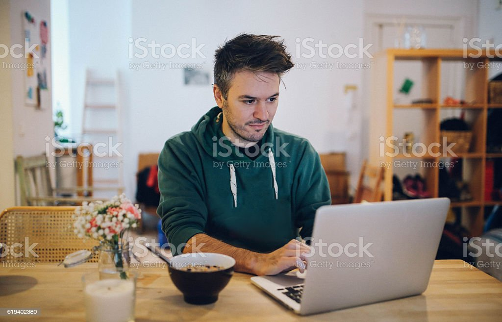 Young man having breakfast and working at home stock photo