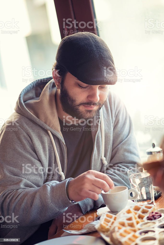 Young Man Having Coffee and Waffles for Breakfast at Restaurant stock photo