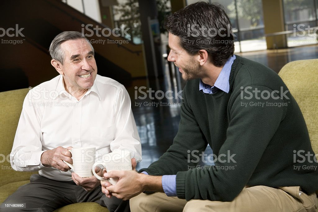 Young Man Having Coffee With a Senior Friend royalty-free stock photo