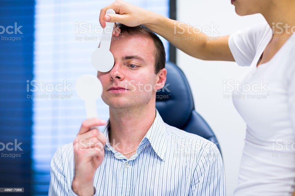 Young man having his eyes examined by optometrics stock photo