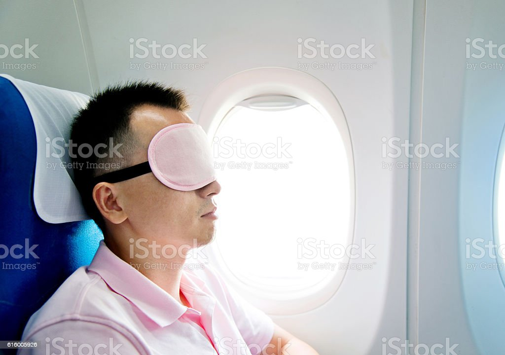 Young man having nap in a plane stock photo