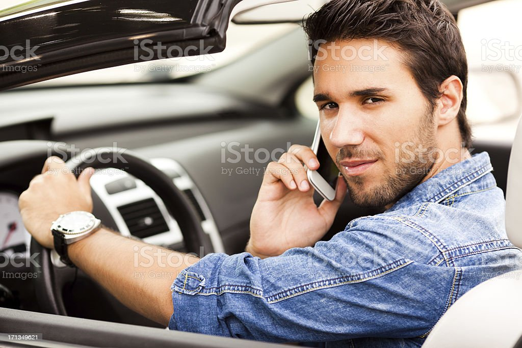 Young man having phone conversation in his car stock photo