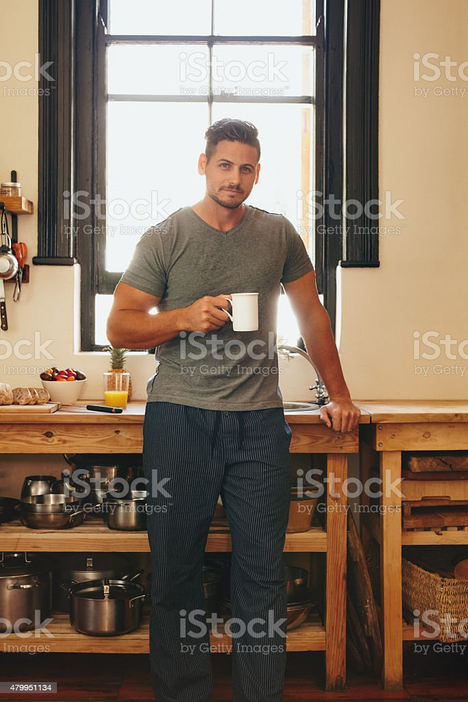 Young man having refreshing coffee in morning stock photo