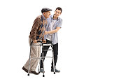 Young man helping an elderly man with a walker