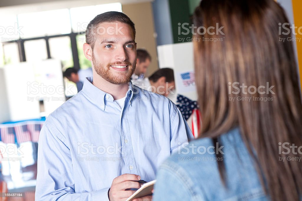 Young man helping woman at an election voting center stock photo