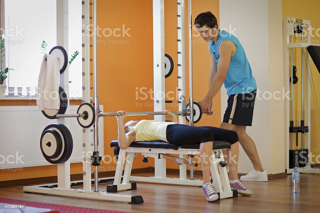 Young man helping young woman lift barbell on bench stock photo