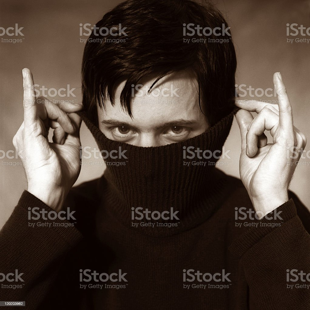 Young Man Hiding Face Inside Turtle Neck Sweater, Sepia Toned stock photo