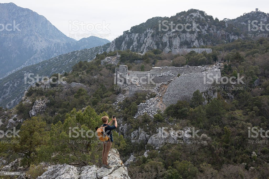 Young man hiking above theatre, ancient Greek ruin stock photo