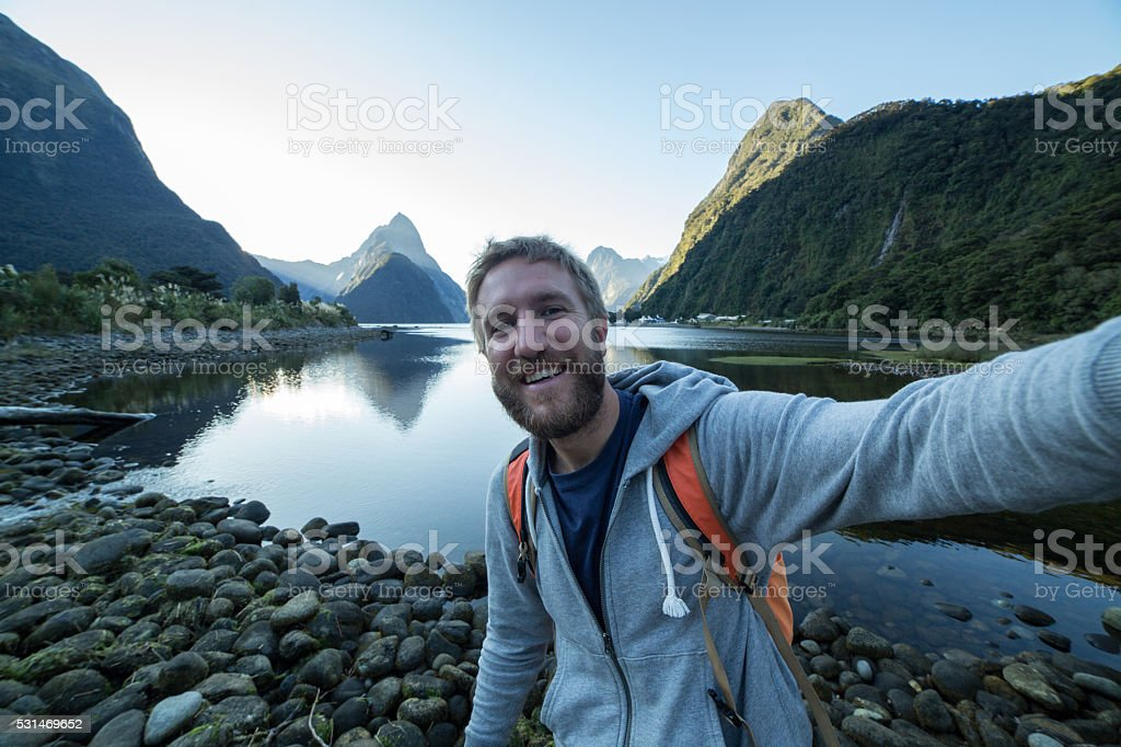 Young man hiking, captures selfie in Milford sound stock photo