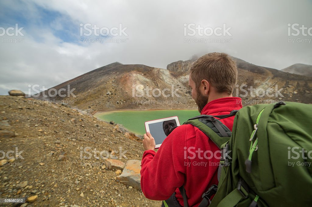 Young man hiking consults a digital map-New Zealand stock photo