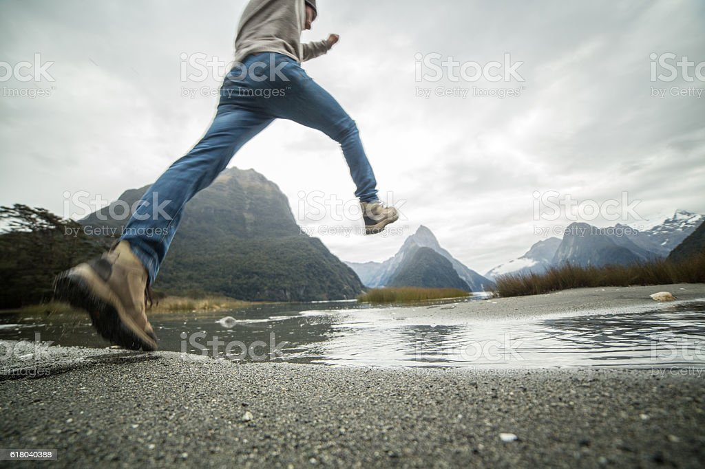 Young man hiking jumps over the mountain river stock photo