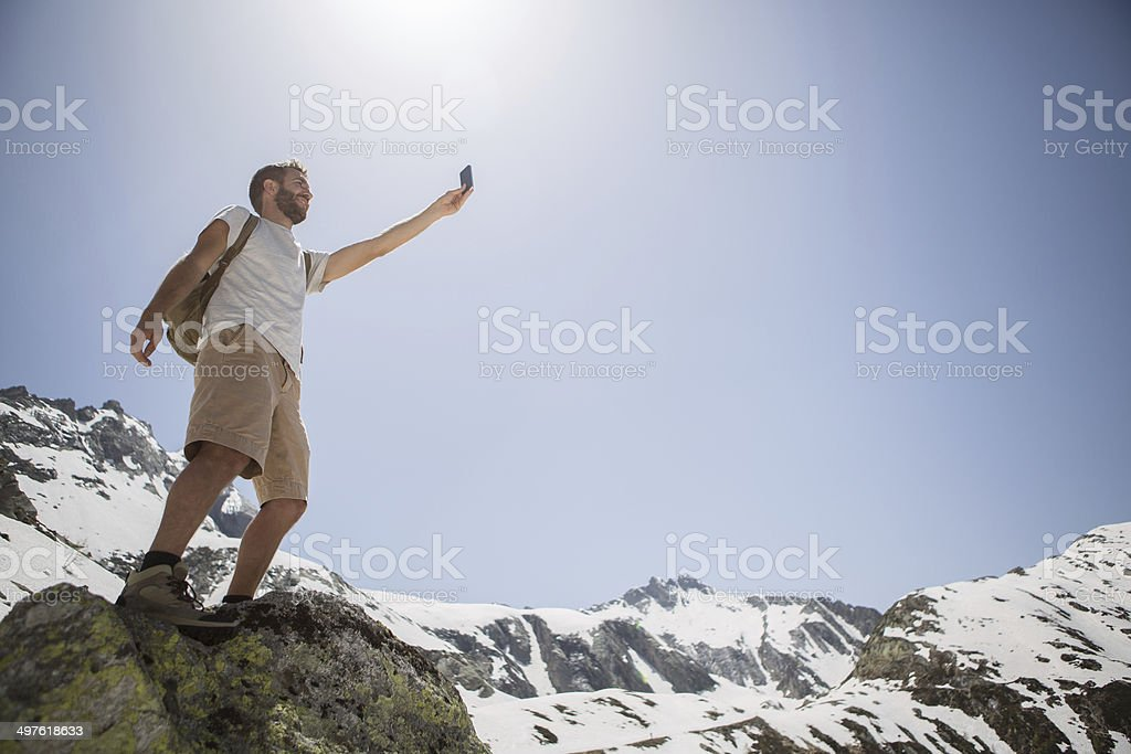 Young man hiking on cliff taking a selfie stock photo