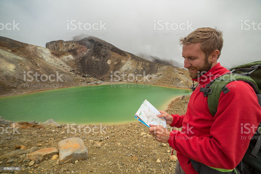 Young man hiking reads a map stock photo