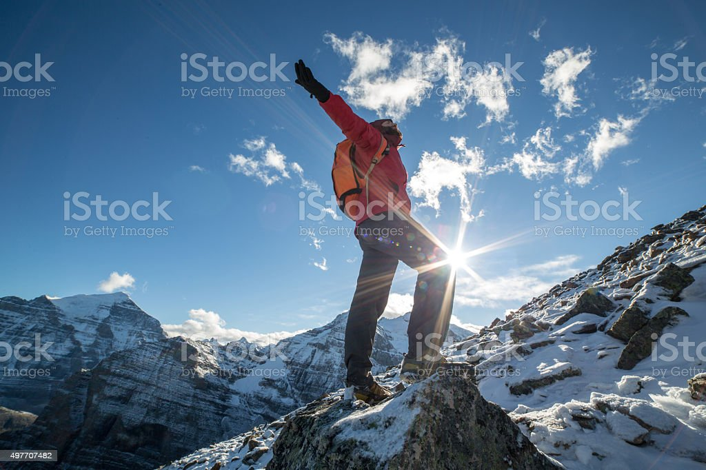 Young man hiking stands on a mountain top arms outstretched stock photo