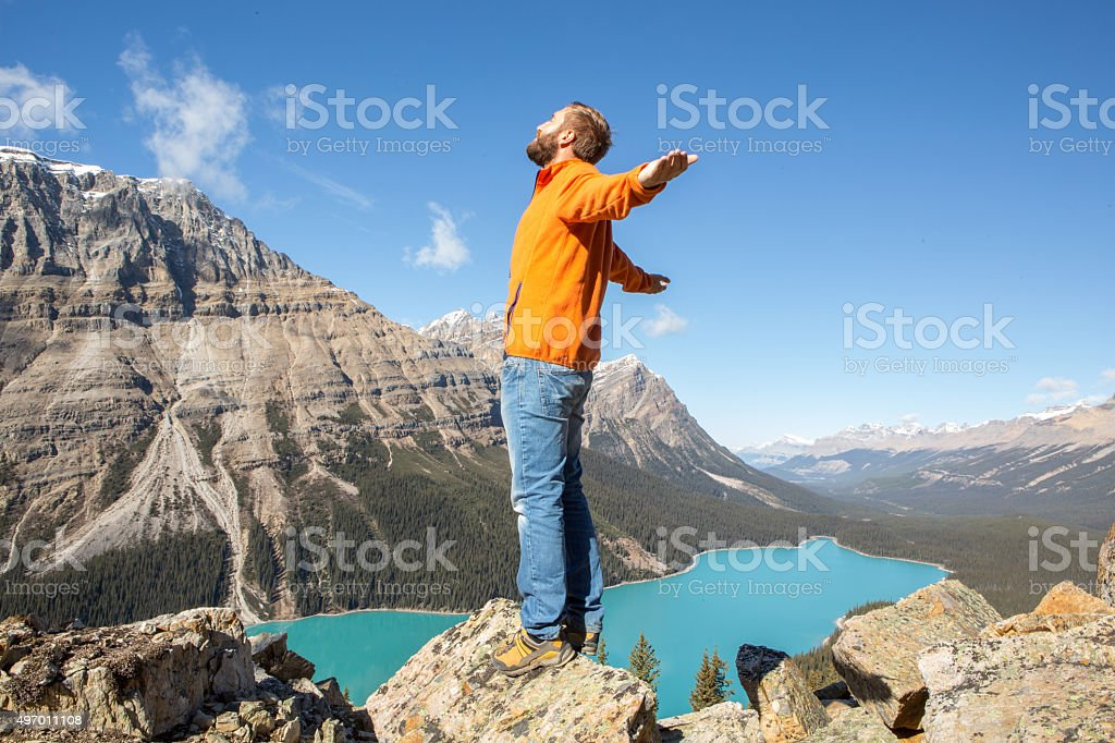 Young man hiking stands on mountain top arms outstretched stock photo