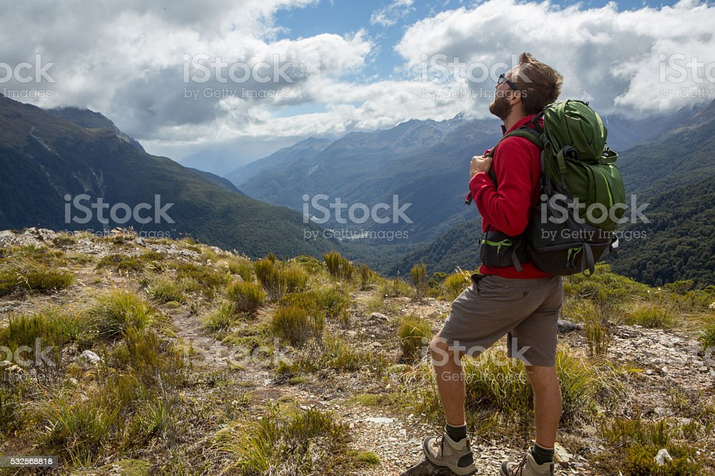 Young man hiking stops to look at mountain landscape stock photo
