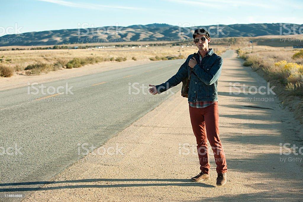 Young man hitchhiking at roadside stock photo