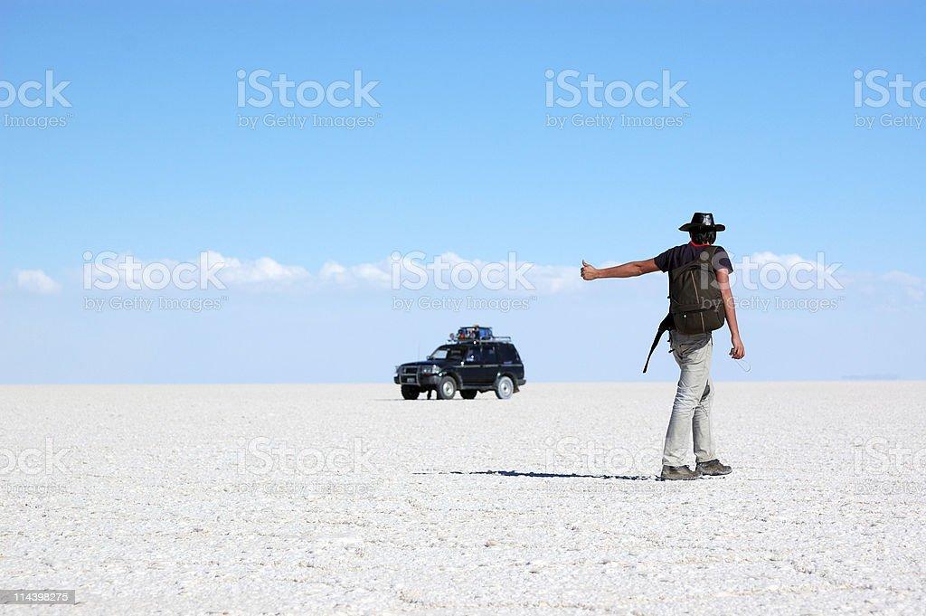 Young man hitchhiking in salt desert royalty-free stock photo