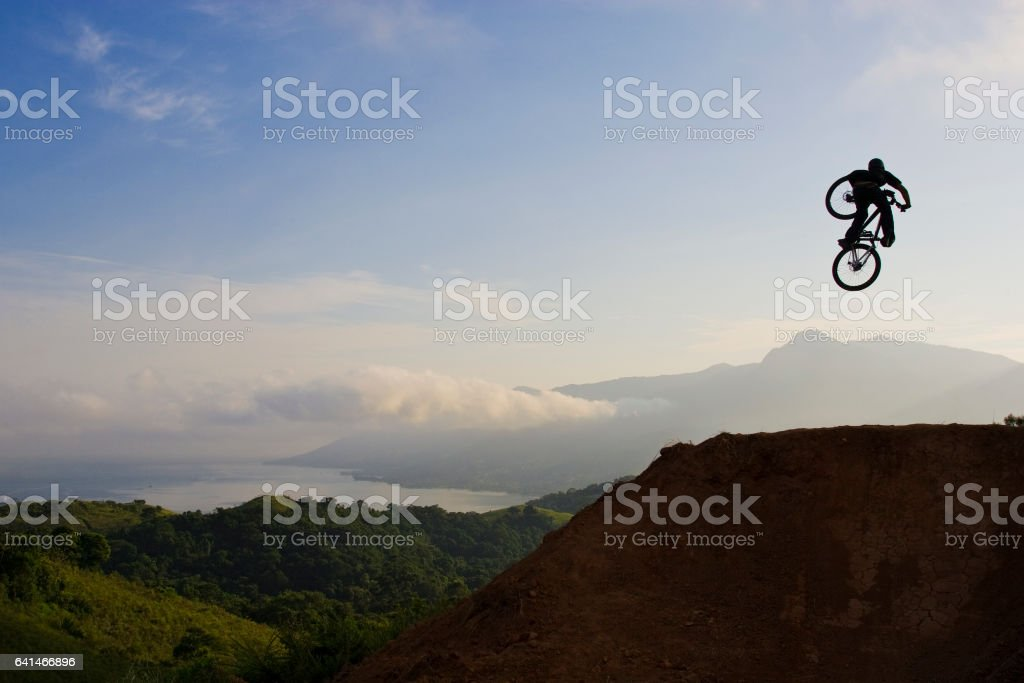 A young man hits a big jump on his mountain bike early in the morning. stock photo