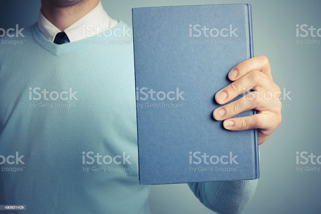 Young man holding a big book stock photo
