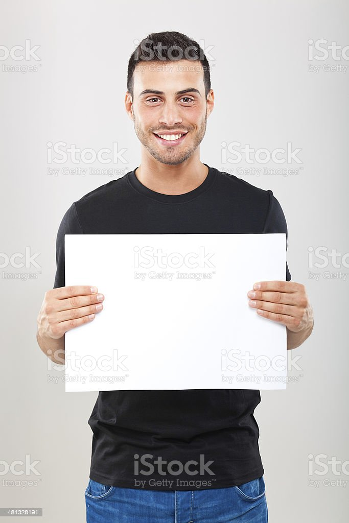 Young man holding a blank sheet stock photo