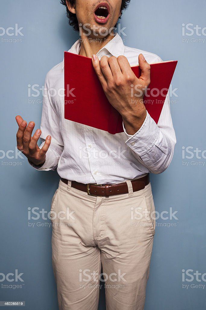 Young man holding a book and singing stock photo