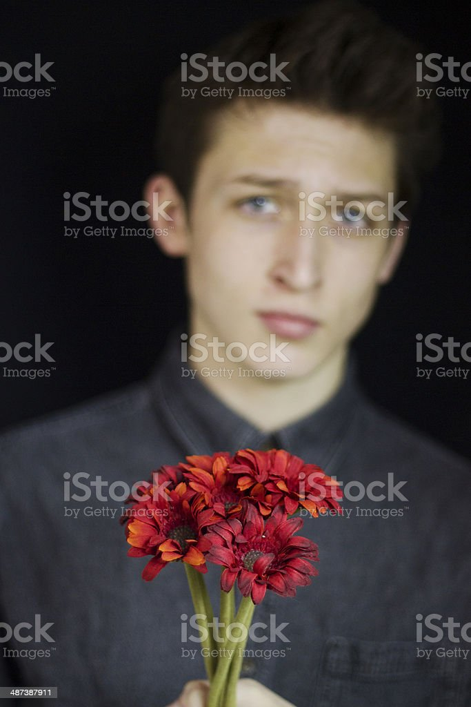 Young man holding a bouquet of flowers royalty-free stock photo