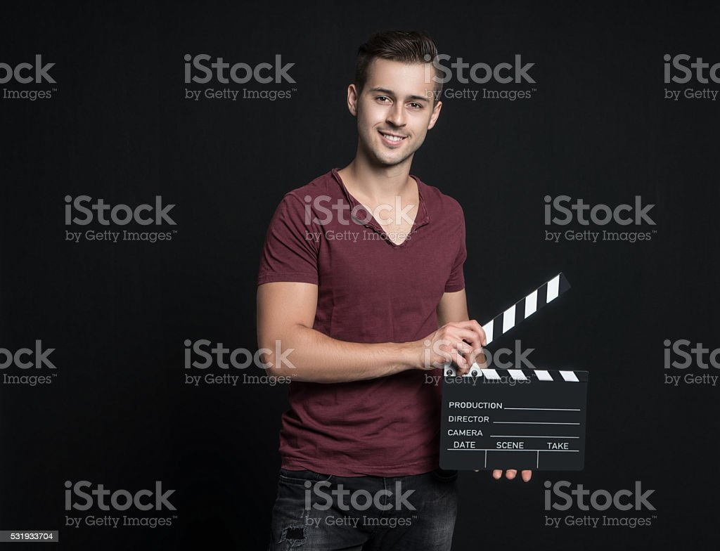 Young man holding a clapperboard stock photo
