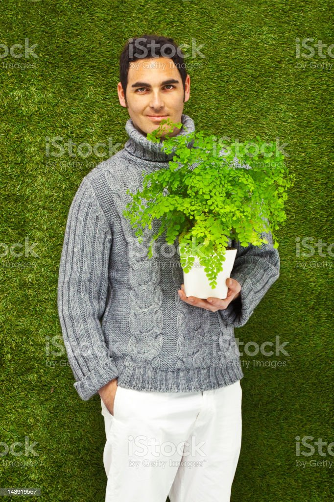 Young man holding a fresh plant, thinking green stock photo