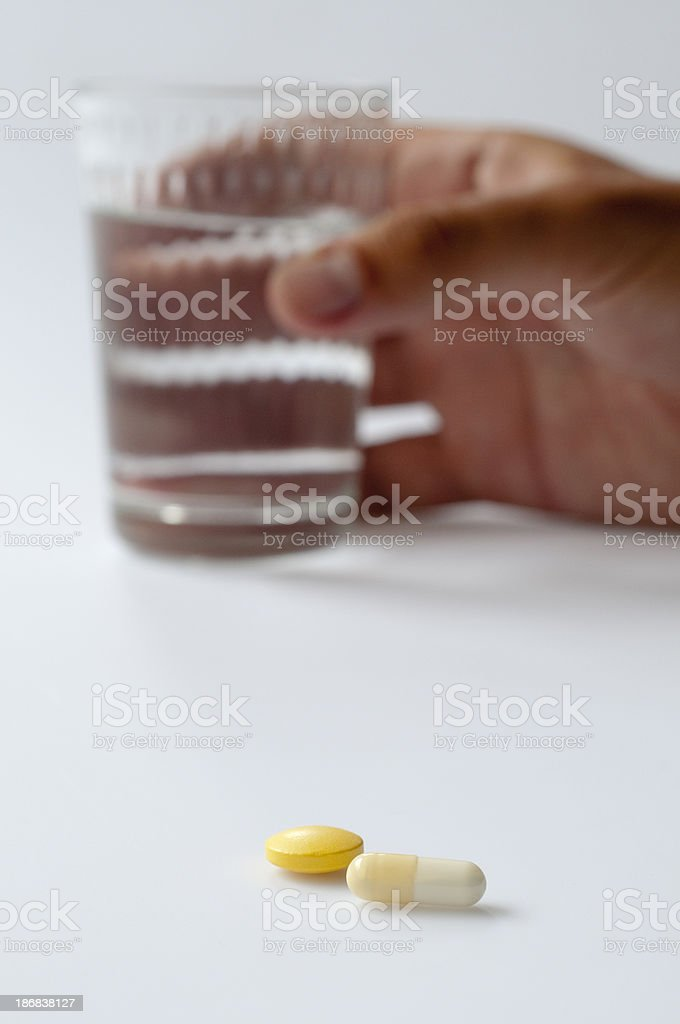 Young man holding a glass of water next to pills royalty-free stock photo