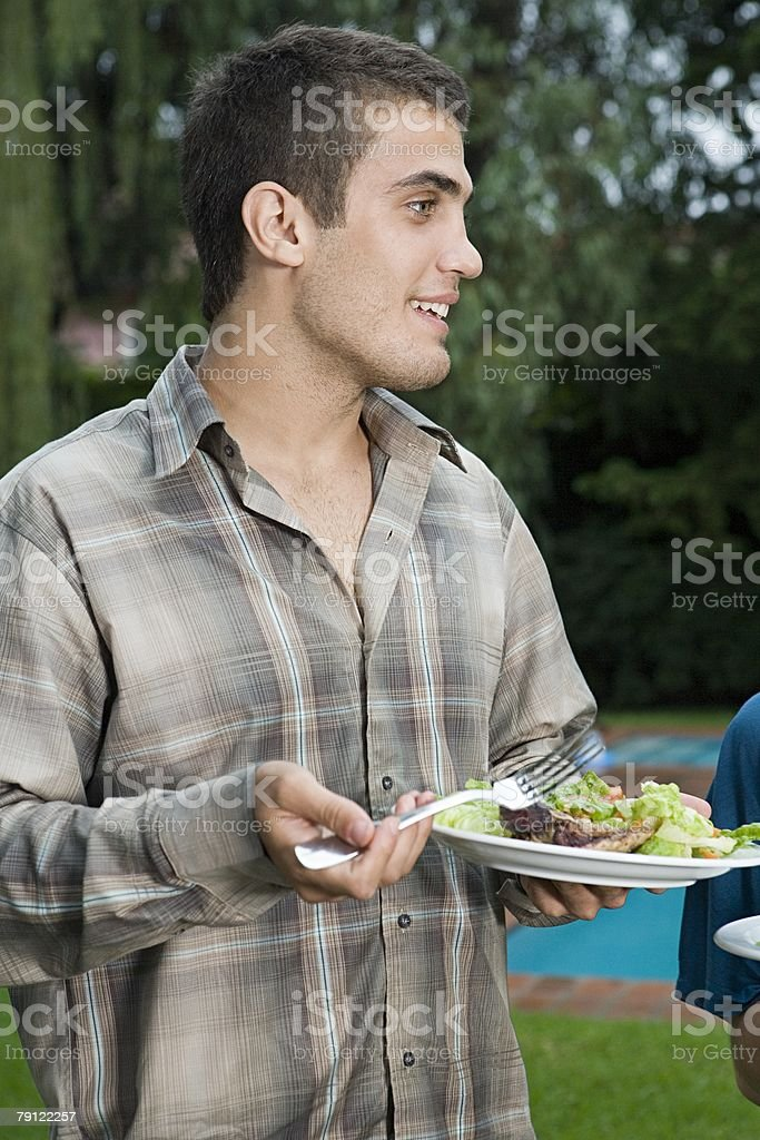 Young man holding a plate of food royalty-free stock photo