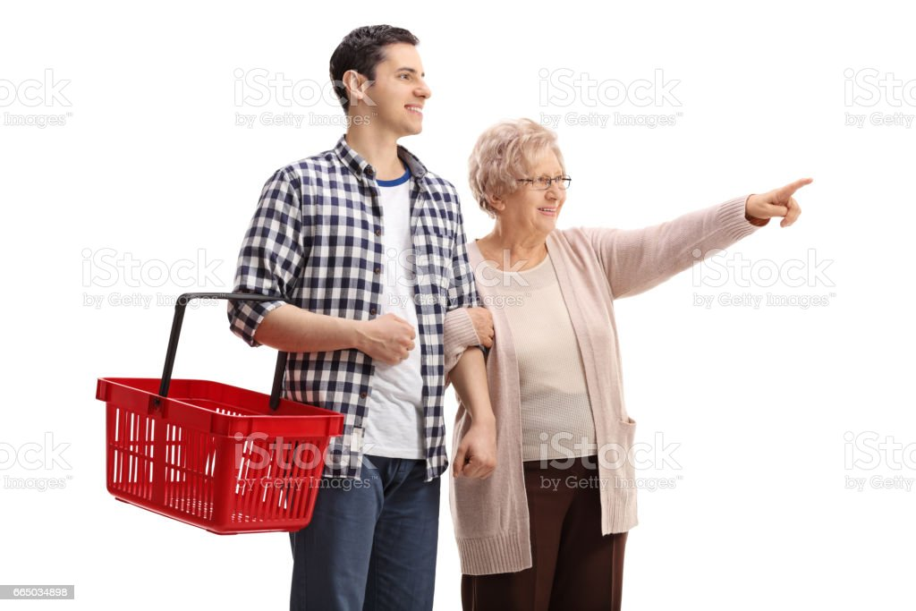 Young man holding a shopping basket with elderly woman pointing stock photo