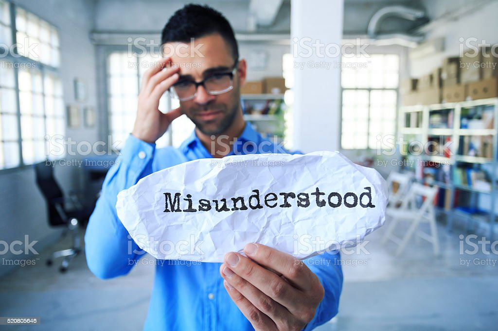 Young man holding a sign 'misunderstood' stock photo