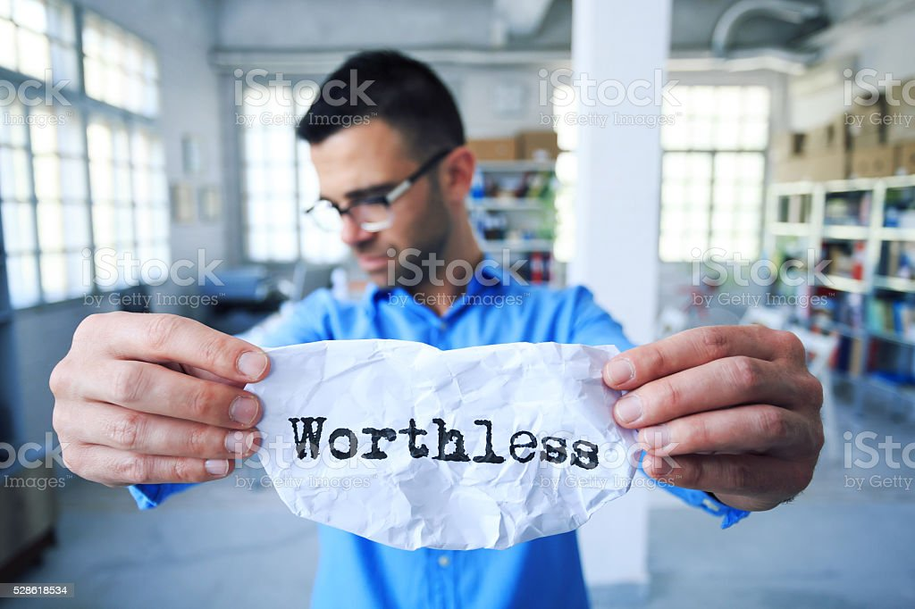 Young man holding a sign 'worthless' stock photo