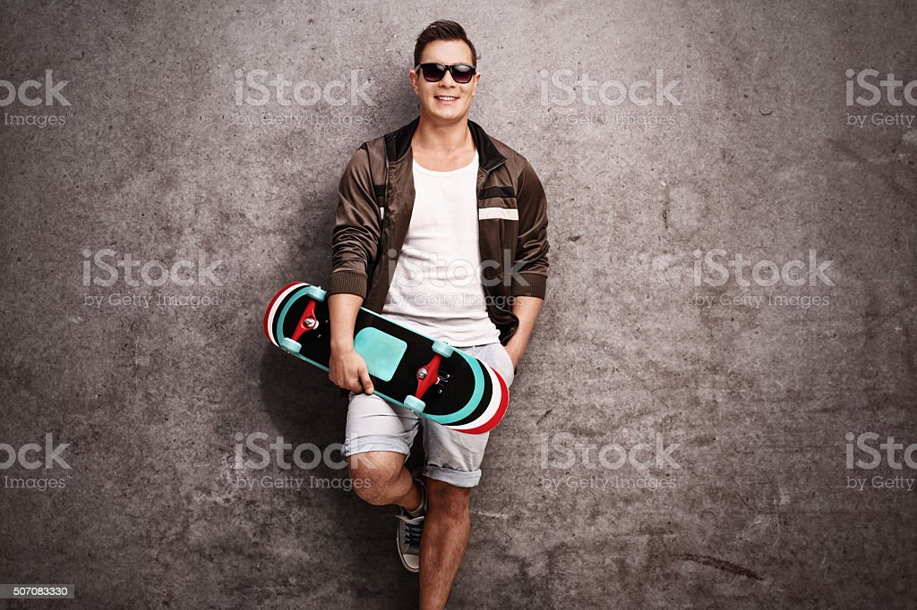 Young man holding a skateboard stock photo