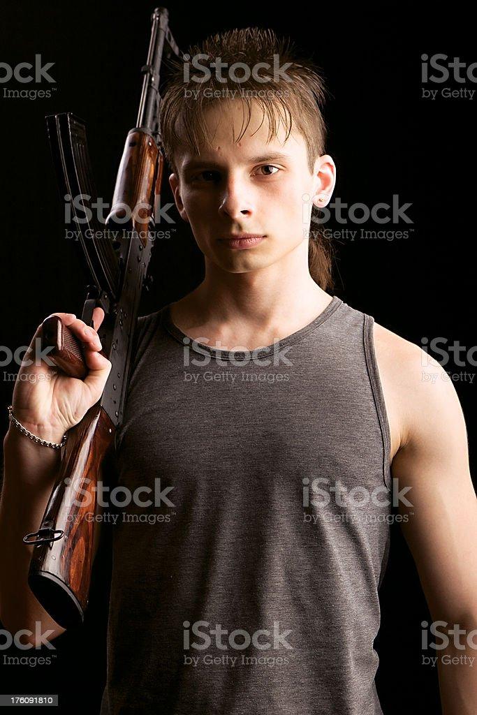 Young man holding AKM automatic rifle stock photo