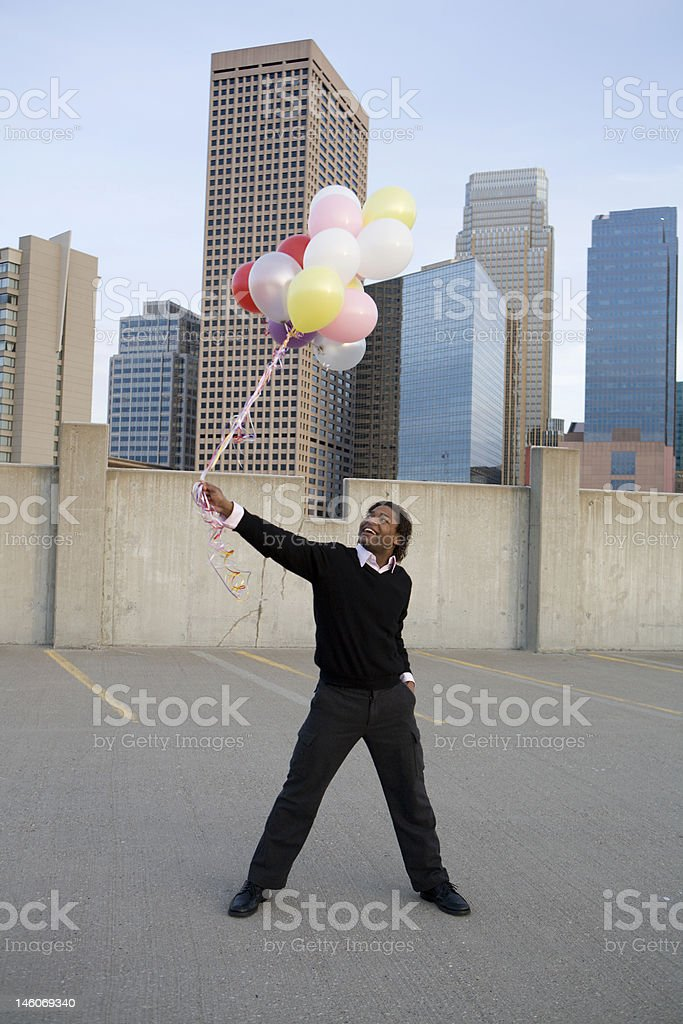 Young Man Holding Balloons In Parking Garage royalty-free stock photo